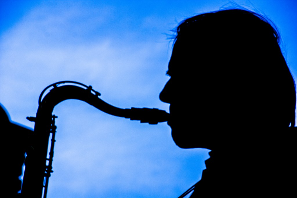 A silhouetted sax man wails on his horn at the first Brews & Blues Bash on N. Front Street.
