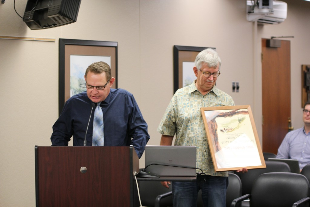 "Communications & Public Affairs Director Randy Beehler addresses the Yakima City Council as Yakima Valley Museum Director John Ball looks at an original signed poster from the classic movie ""The Hanging Tree"" that was recently donated to the Museum by The City of Yakima."