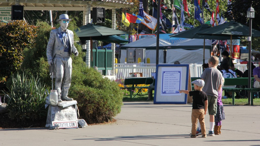 "Three young fans can't quite figure out what to think of  ""Mr. Statue"" performing near the Gazebo at the Central Washington State Fair."