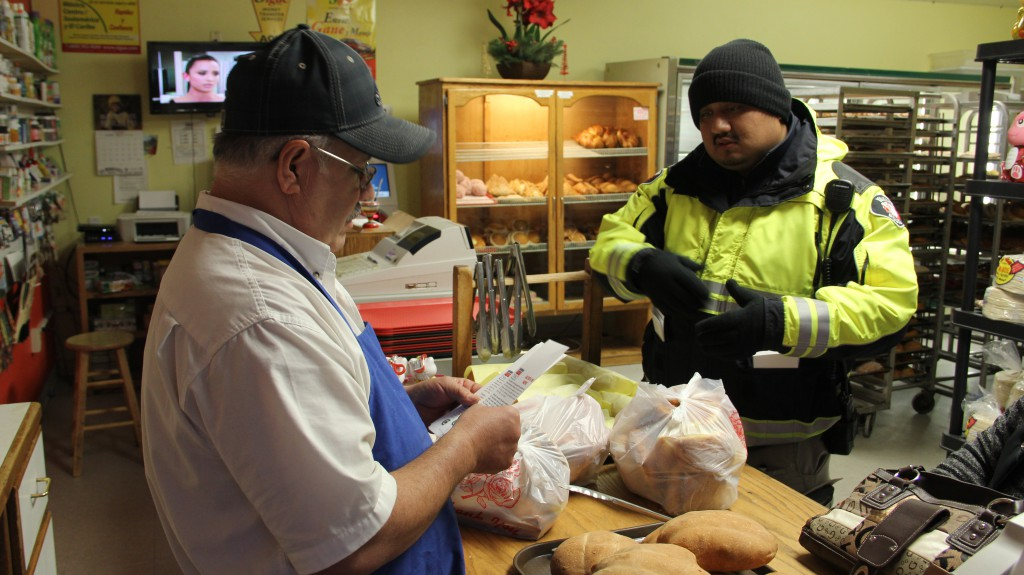 Parking Enforcement Officer Luis Torrico hands out and explains Snow Alert and Snow Route information to a local panaderia in Downtown Yakima with winter weather forecasted for Yakima.