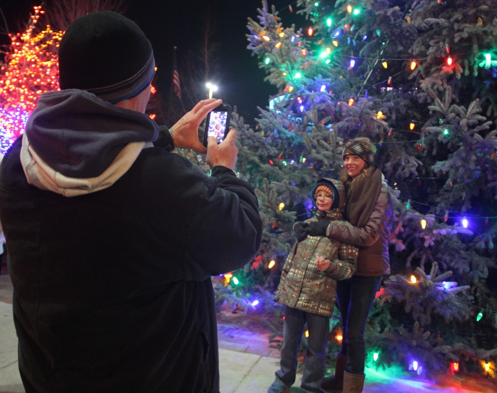 A father takes a snapshot in front of the Community Christmas Tree at one of the recent holiday events downtown.