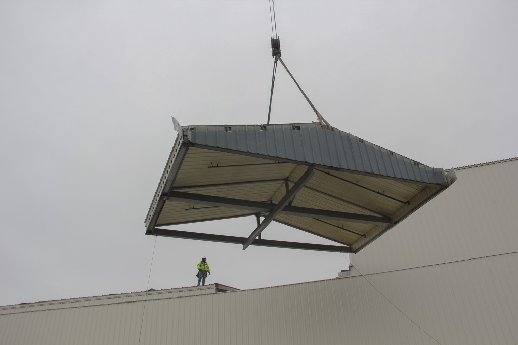 A section of the roof at Shields Bag and Printing is hoisted back in place following a large equipment install at the facility.