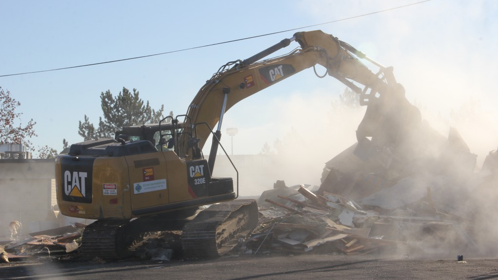 Heavy equipment creates a cloud of dust as it rips through the abandoned Tiger Mart building on 24th and Nob Hill Boulevard to begin the environmental clean up process.