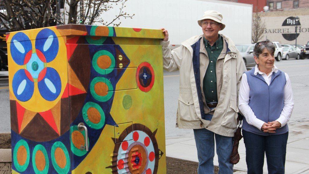 Local artist Stan Hughes and Yakima Arts Commission Chair Noel Moxley stand next to the first installation of the Yakima Arts Commission's latest project, which wraps plain traffic signal boxes in colorful public art.