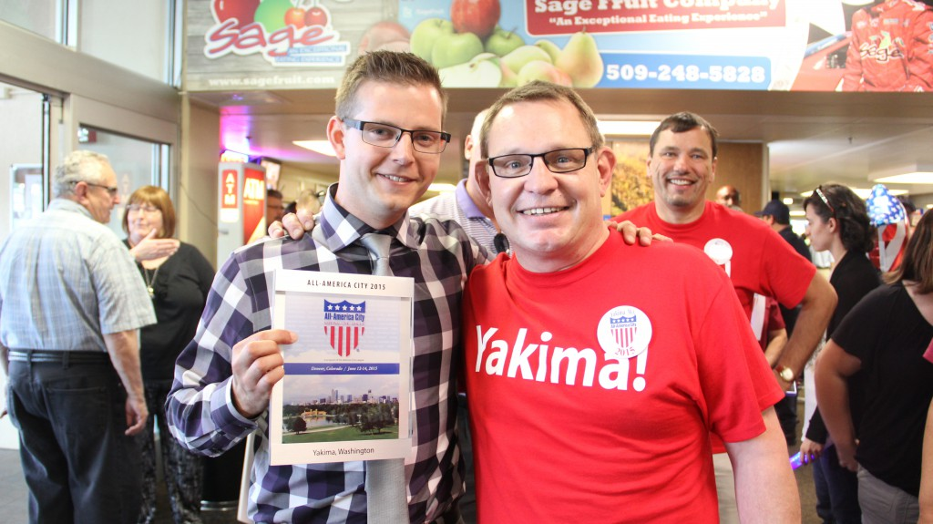 Mayor Cawley poses with and congratulates City of Yakima Communications and Public Affairs Director Randy Beehler who is holding Yakima's 2015 All-America City Award in the Yakima Air Terminal after returning from the competition in Denver, Colorado.