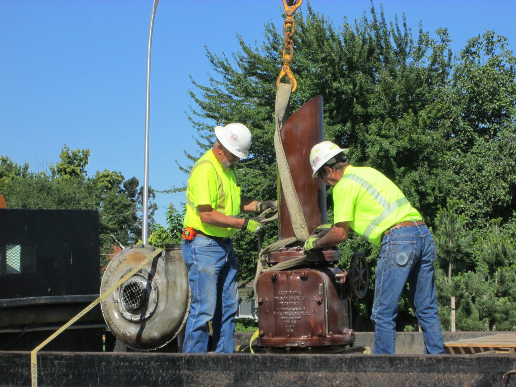 Crews install art work at the Fair Avenue roundabout.