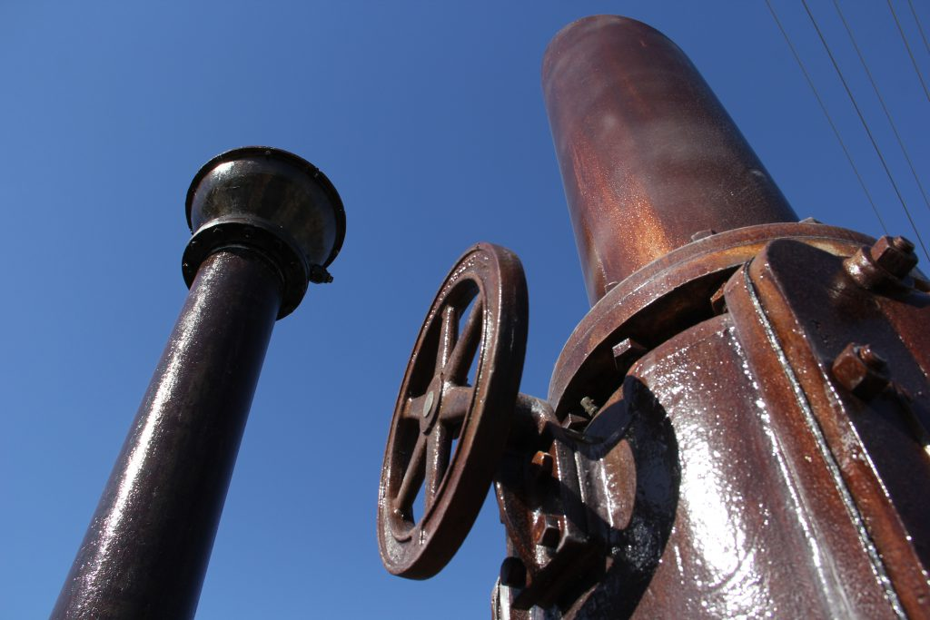 """Old pieces of machinery from the Cascade Mill are now prominently displayed as public artwork called """"Pieces of the Past"""" as the centerpiece of the new Fair Avenue Roundabout."""