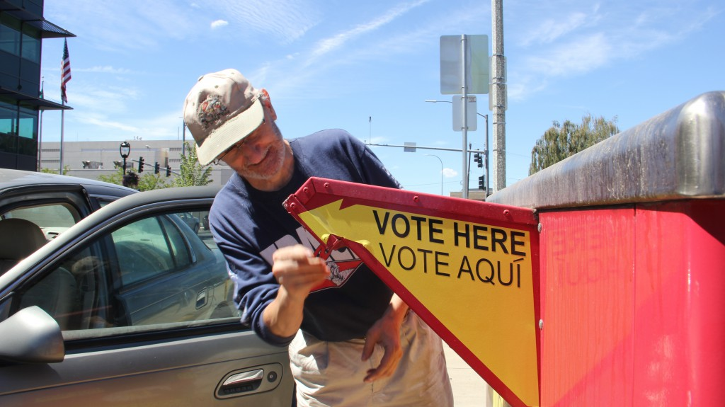 A registered voter saves a stamp and drops his primary election ballot at a collection box just down the street from Yakima City Hall.