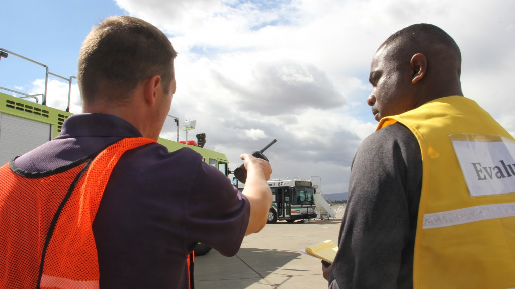 Airport Manager Rob Peterson describes the scene to an evaluator during a full scale live emergency exercise at the Yakima Airport.