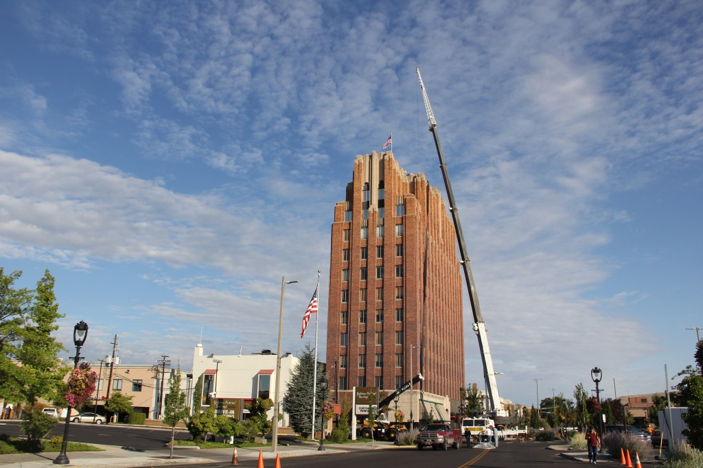 A crane stretches above the Larson Building lifting communications equipment for Radio Yakima's downtown relocation.