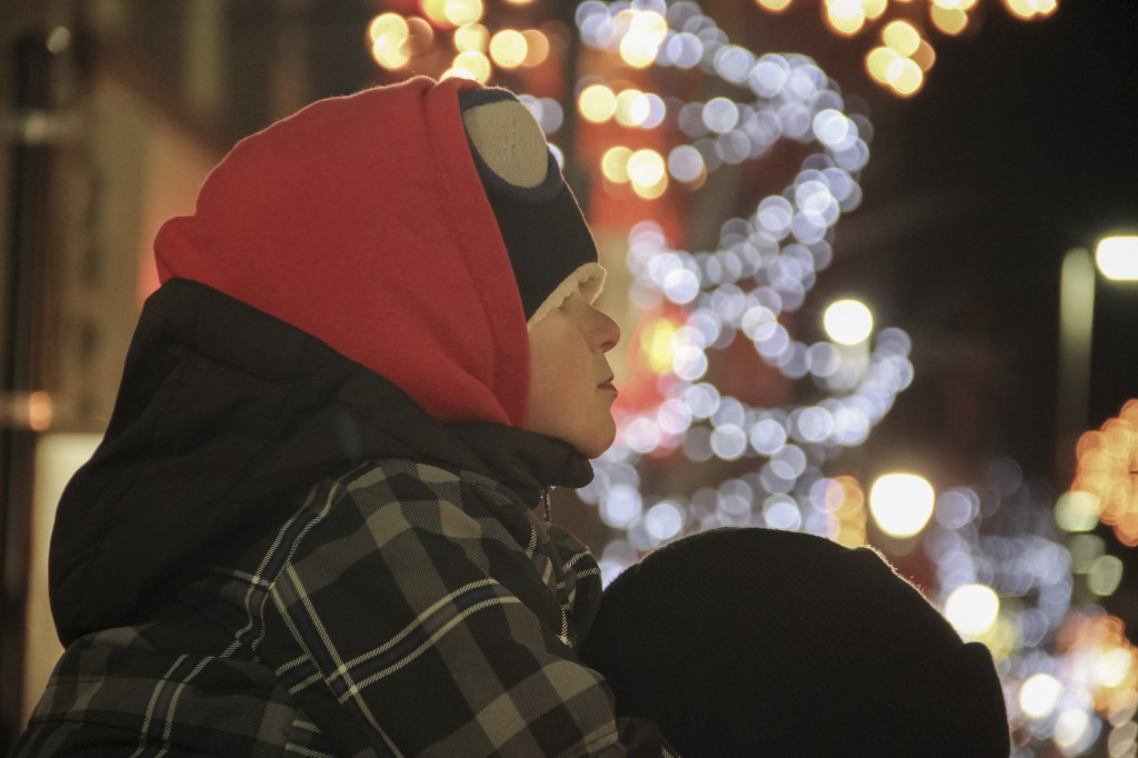 Jackson Brannum contently watches the 14th Annual Holiday Light Parade in Downtown Yakima from atop his dad Brian's Shoulders.